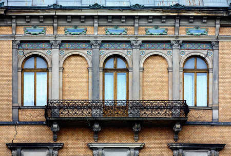Wrought balcony in old style as part of a building photo