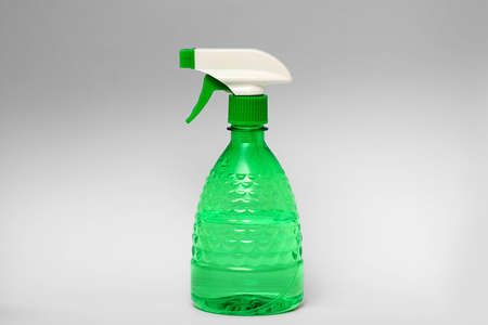 Green spray bottle made of clear plastic isolated on grey background Stock Photo
