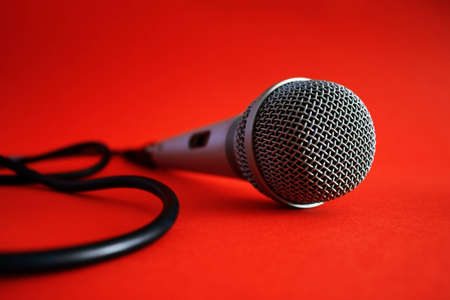 Close up of professional silver microphone with wire on red background Stock Photo
