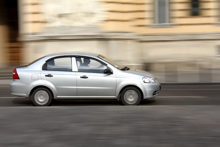 panning: Silver car going at high speed in the street with panning effect