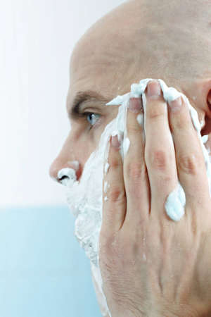 Young man applying shaving foam to face photographed in profile
