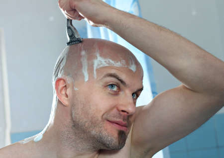 Caucasian man shaving head in the bathroom Stock Photo