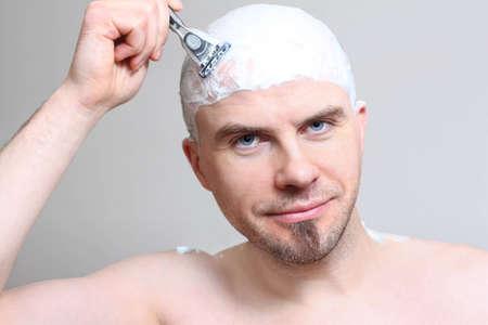 Young man with razor shaving head