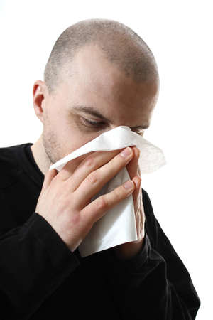 alergy: Young man feeling sick blowing nose