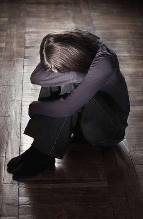 mujer llorando: Niña sentada en el piso sucio de llorar Foto de archivo
