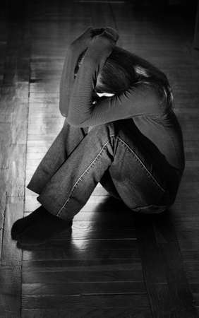 Upset young woman sitting lonely on the floor