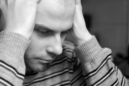 Caucasian man sitting with head in hands looking depressed Stock Photo
