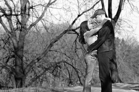 Young man and woman standing in a hug looking at each other in park Stock Photo - 12866076