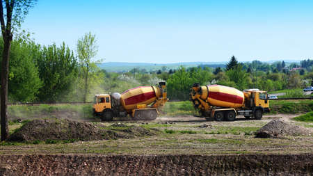 Two concrete mixer lorries working at building site Stock Photo