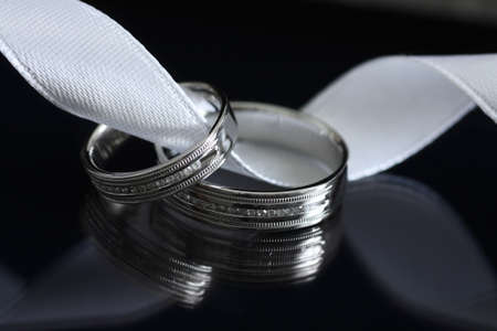 Two wedding rings made of white gold on black background with reflection Stock Photo