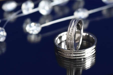 Pair of white gold wedding rings with diamonds on dark background