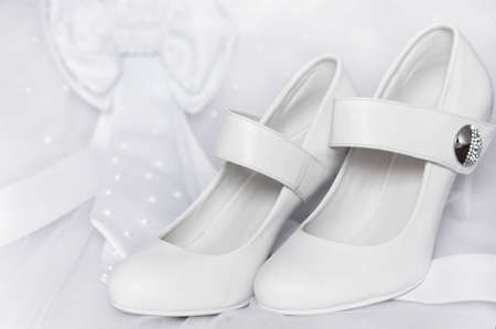 Pair of white wedding shoes on heels