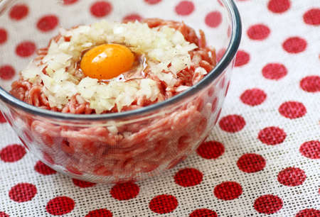 mincemeat: Raw pork mincemeat with egg and chopped onion in a clear glass  bowl Stock Photo