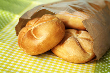 Three small buns made of white flour in paper bag