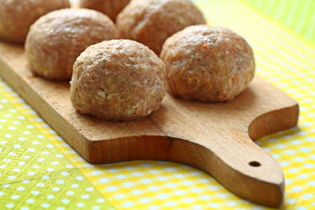 Six beef balls from minced meat laid on wooden cutting board