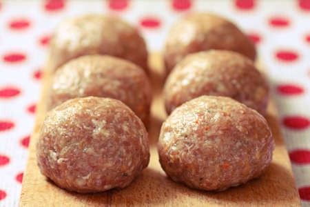 Six beef balls from minced meat laid on wooden cutting board photo