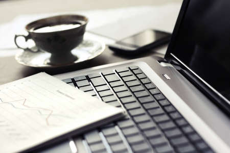 Close up of computer with financial statement and cup of coffee