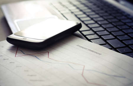 Close up of laptop with financial statement and mobile phone