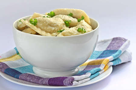 Traditional cooked polish dumplings in white bowl Stock Photo