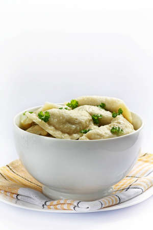 Traditional cooked polish dumplings in white bowl photo
