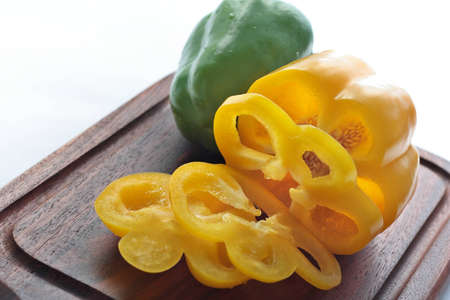 Yellow and green sweet peppers on chopping board Stock Photo - 14127688