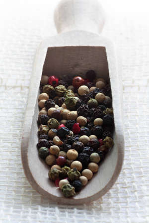 Close up of assorted peppercorns on measure wooden spoon Stock Photo - 14127690
