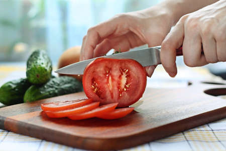 Caucasian female hands cutting red tomato on chopping board
