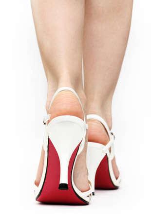 tacones: Cierre de las mujeres cauc�sicas en los pies sandalias de encaje blanco con una caminata �nica de color rojo sobre fondo blanco