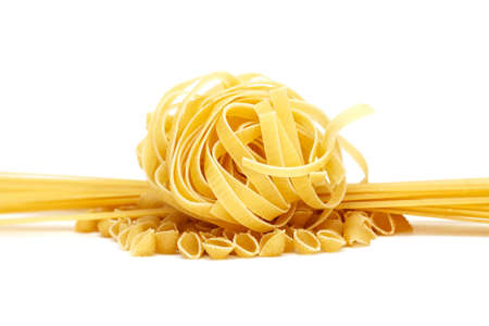 Selection of three types of pasta linguine, shells and tagliatelle on white background