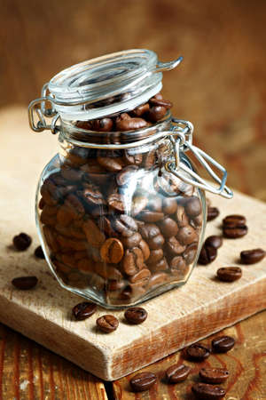 Close up of roasted coffee beans in a clear glass jar on a wooden board