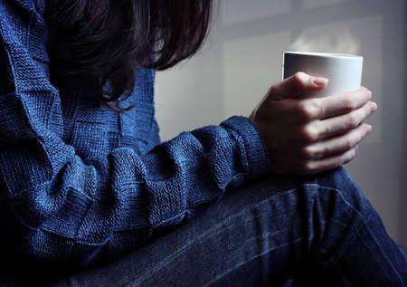 fille triste: Jeune femme assise et attend avec une tasse de boisson chaude dans ses mains Banque d'images