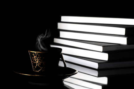 Cup or hot coffee with steam placed in front of large pile of books on black background