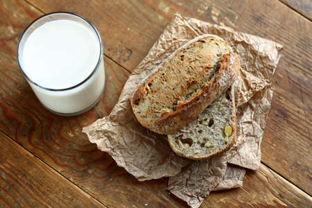 Top view on cut in halves whole grain bread roll and a glass of milk
