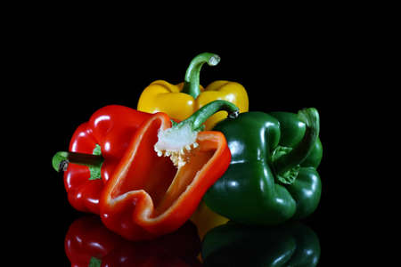 Four bell peppers red, green and yellow with one cut in half on black background with reflection Stock Photo