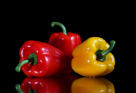 red peppers: Three bell peppers red and yellow on black background with reflection Stock Photo