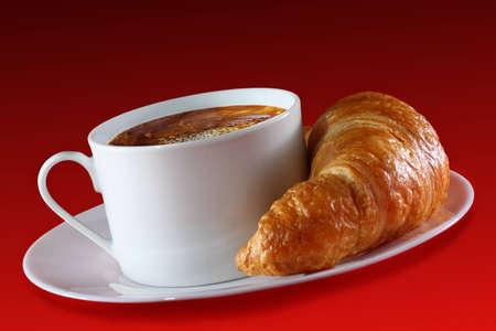 pasteleria francesa: Taza de caf� caliente y un croissant crujiente en el lado sobre fondo rojo