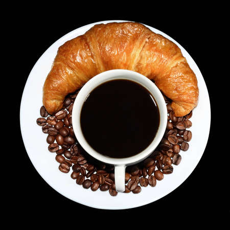 Top view of cup of hot coffee with beans and a crunchy croissant on the side on black background