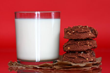 Close up of glass filled with milk and stack of cookies Stock Photo