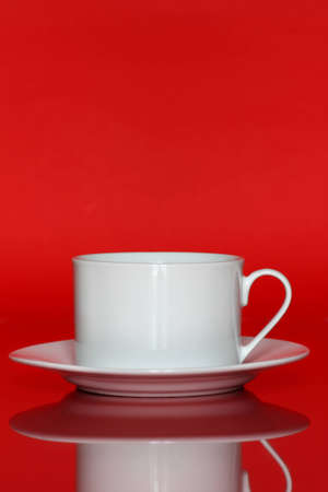 White porcelain cup with saucer over red background