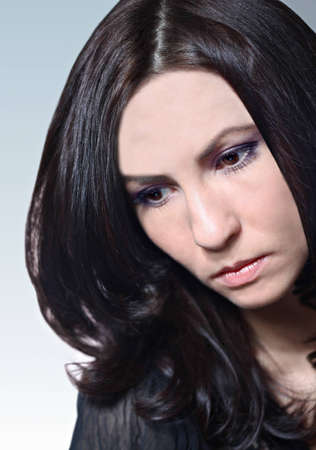 Young caucasian woman with dark long hair looking sad