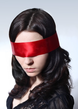 Portrait of a young Caucasian female with brown hair and red blindfolder over her eyes Stock Photo