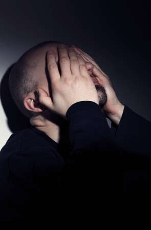 Close up of a Caucasian man covering face with hands from desperation