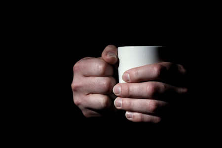 Close up of male hands holding mug with coffee or tea on black background Stock Photo