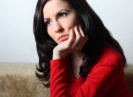 Young good looking brunette with long hair sitting supporting her head with hand Stock Photo
