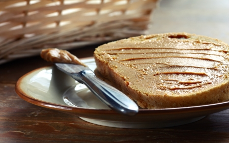 Peace of white bread spread with peanut butter with knife on the plate Stock Photo