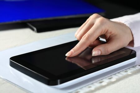 Close up of female hands touching tablet computer