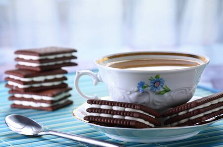 Close up of cup of hot tea and chocolate biscuits