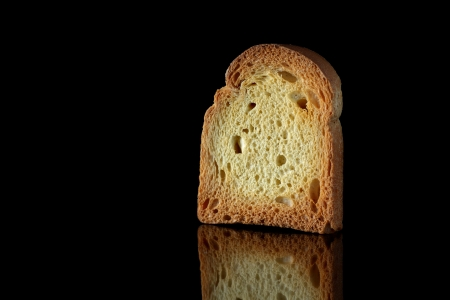 Close up of golden slice of toast on black background with reflection