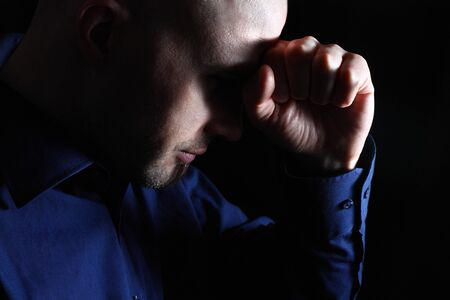 Anxious white man low key portrait