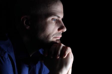 Caucasian man looking depressed close up on black background